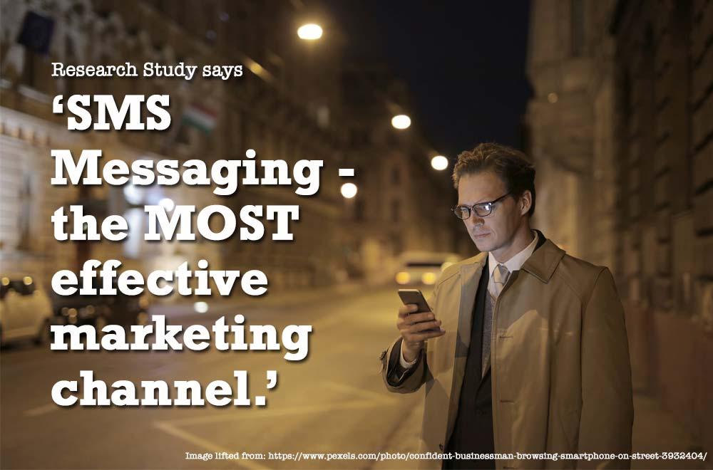 SMS Marketing confident businessman browsing thru a smartphone on street